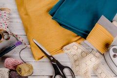 有五颜六色的布料的缝合的工具在一个木板 库存图片