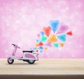 有五颜六色的心脏爱气球的桃红色滑行车玩具在木tabl 图库摄影