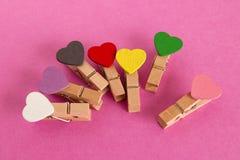 有五颜六色的心脏的木别针在桃红色背景 免版税库存照片