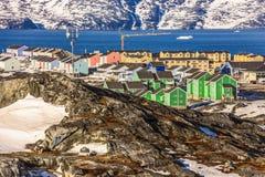 有五颜六色的房子的努克市在雪盖了用海的海湾 图库摄影