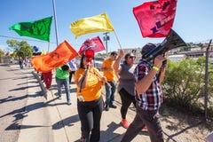 有五颜六色的旗子的行军者在边界抗议 免版税库存图片