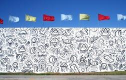 有五颜六色的旗子的街道画墙壁 免版税图库摄影