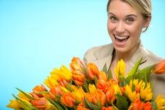 有五颜六色的春天郁金香的快乐的妇女 图库摄影