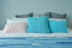 有五颜六色的枕头的蓝色色彩设计少年卧室 库存照片