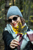 有五颜六色的枫叶的年轻白种人妇女在秋天自然 免版税图库摄影