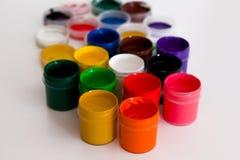 有五颜六色的树胶水彩画颜料的一些个开放罐头 免版税库存图片
