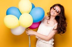 有五颜六色的气球的十几岁的女孩,演播室射击 图库摄影