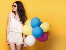 有五颜六色的气球的十几岁的女孩,演播室射击 免版税库存照片