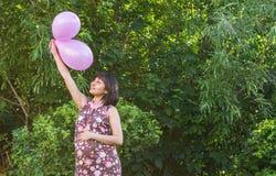 有五颜六色的气球的孕妇在夏天公园 库存照片