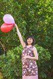 有五颜六色的气球的孕妇在夏天公园 免版税库存图片