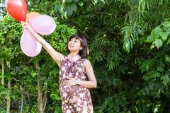有五颜六色的气球的孕妇在夏天公园 免版税图库摄影