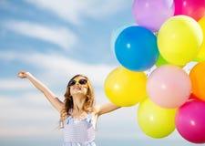 有五颜六色的气球的愉快的女孩 图库摄影