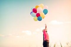 有五颜六色的气球的愉快的少妇,在早晨时间享用在草原 图库摄影