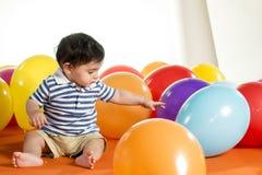 有五颜六色的气球的愉快的男孩在白色 免版税库存照片
