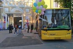 有五颜六色的气球的黄色公共汽车站立在书陈列在武库博物馆在基辅 免版税图库摄影