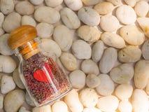 有五颜六色的沙子的一个装饰爱玻璃瓶里面在白色石头背景 库存照片