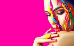 有五颜六色的油漆的秀丽式样女孩在她的面孔 美丽的妇女画象有流动的液体油漆的 免版税库存照片
