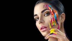有五颜六色的油漆的秀丽式样女孩在她的面孔 美丽的妇女画象有流动的液体油漆的 图库摄影