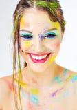 有五颜六色的油漆的美丽的微笑的女孩在面孔飞溅 免版税图库摄影