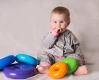 有五颜六色的玩具的逗人喜爱的婴孩在灰色背景 库存照片