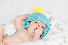 有五颜六色的盖帽的新出生的婴孩 免版税库存图片