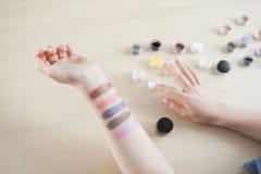 有五颜六色的眼影膏污迹的女性手 图库摄影