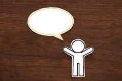 有五颜六色的空白的对话讲话泡影的纸人在棕色木头 黑色通信概念收货人电话 库存图片