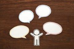 有五颜六色的空白的对话讲话的纸人在棕色木头起泡 黑色通信概念收货人电话 免版税图库摄影