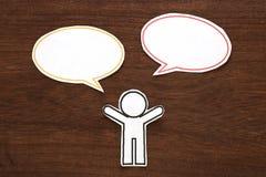 有五颜六色的空白的对话讲话的纸人在棕色木头起泡 黑色通信概念收货人电话 免版税库存图片