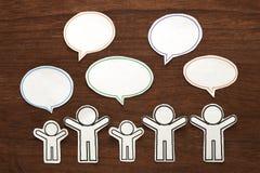 有五颜六色的空白的对话讲话的纸人在棕色木头起泡 黑色通信概念收货人电话 库存图片