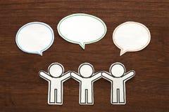 有五颜六色的空白的对话讲话的纸人在棕色木头起泡 黑色通信概念收货人电话 图库摄影