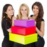有五颜六色的箱子的三个女孩 库存照片