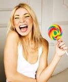 有五颜六色的糖果愉快微笑的,情感摆在,生活方式人概念年轻人相当白肤金发的女孩 免版税库存图片
