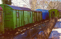 有五颜六色的老火车,木,有削皮油漆的无盖货车在gre 免版税库存照片