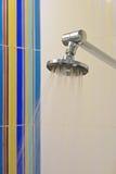 有五颜六色的背景瓦片的淋浴喷头 免版税库存图片