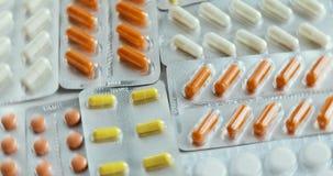 有五颜六色的胶囊的水泡 照相机迅速批评片剂一张顶视图  转动的圆药物 上色了许多药片 股票视频