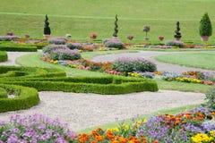 有五颜六色的花和黄杨木潜叶虫的现代亚洲庭院。 免版税库存照片