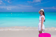 有五颜六色的行李的年轻美丽的妇女在热带海滩 免版税库存图片