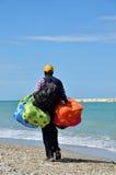 有五颜六色的袋子的一位推销员在海滩 免版税库存图片