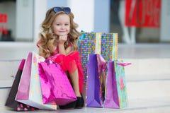 有五颜六色的袋子的逗人喜爱的小女孩购物的在超级市场 免版税库存照片