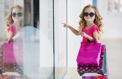 有五颜六色的袋子的逗人喜爱的小女孩购物的在超级市场 免版税库存图片