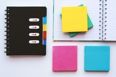 有五颜六色的被关闭的和被打开的笔记本在白色桌上的稠粘的笔记薄 库存图片