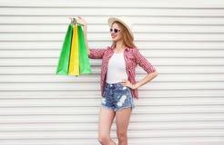 有五颜六色的购物带来的愉快的微笑的年轻女人在夏天回合草帽,方格的衬衣,在白色墙壁上的短裤 免版税库存照片