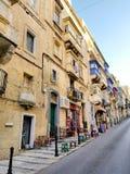 有五颜六色的阳台的典型的瓦莱塔街道爬上的门面的 免版税库存照片