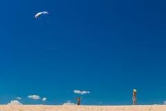 有五颜六色的风筝的男孩反对在海滩的蓝天 图库摄影