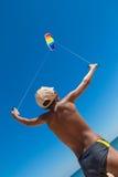 有五颜六色的风筝的男孩反对在海滩的蓝天 免版税库存图片