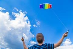 有五颜六色的风筝的男孩反对蓝天 免版税图库摄影