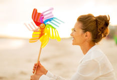有五颜六色的风车玩具的妇女坐海滩 免版税库存图片