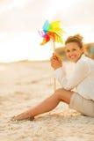 有五颜六色的风车玩具的妇女坐海滩 库存照片
