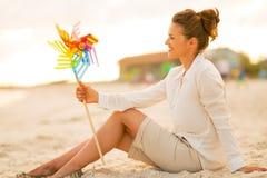 有五颜六色的风车玩具的妇女坐海滩 免版税库存照片